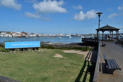 Photography of a wooden pier and a gazebo and the boats anchored at  the port of Punta del Este City, Uruguay and a sign saying Port of Punta del Este in spanish