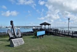 Photography of a wooden pier and a gazebo and the boats anchored at  the port of Punta del Este City, Uruguay and a sign saying Port of Punta del Este in spanish and an anchor