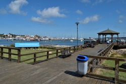 Photography of a wooden pier and a gazebo and the yacths anchored at  the port of Punta del Este City, Uruguay and a sign saying Port of Punta del Este in spanish