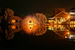 Photography of circular abstract effect of fire lines uses the steel wool firework or steel wool light painting. Fire swirl from steel wool reflection in water at night. SEMARANG, INDONESIA.