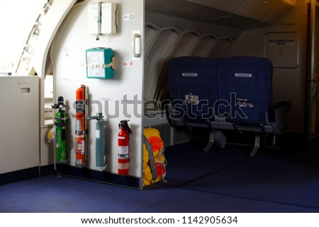 Photography of emergency equipment,extinguisher and first aid kit in aircraft (airplane) at exit door . Emergency radio beacon at aircraft (airplane) exit door.Two passenger seat in aircraft.