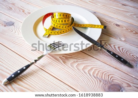 Photography of measuring tape on white plate. Dieting concept image. Diet instead food.