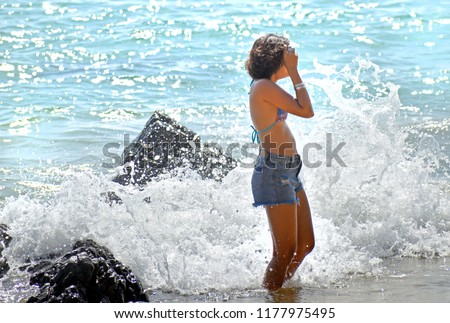 Photography of pretty girl standing standing in the water at the beach with sea wave attack on the beach and the rock background.Sexy cute girl have tan skin in jeans pants and blue swimsuit