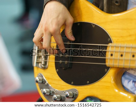 Photography of the musician plays the bass guitar. He picks the strings, clamps the strings on the fretboard. High resolution image.