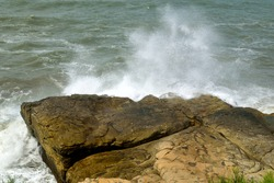 Photography of the waves breaking bravely against a rock at Mar del Plata city