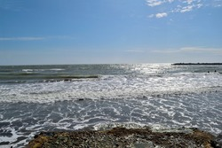 Photography of the wavy sea at the most popular beaches of Mar del Plata City during the summer vacation taken from a pier