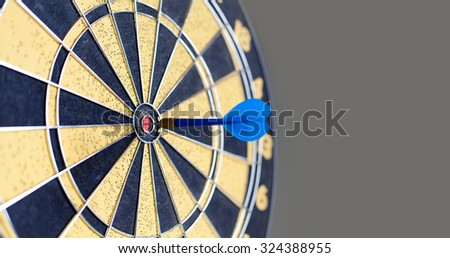 Photography of vintage yellow and black colors darts. Success hitting target aim goal achievement. Blue Dart in bull\'s eye. copy space. soft focus