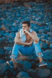 photography of young man on the stone beach. Young man in casual outfit is sitting on the stone beach