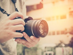 Photography or traveler Concept.The photographer hold DSRL camera in his hands with cityscape blur background and sunlight in summer time, selective focus. Photo of Vintage and filtered process.
