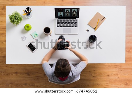 photography, people and technology concept - woman with camera and laptop computer at office table #674745052
