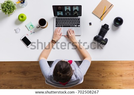 photography, people and technology concept - woman with camera working on laptop at table #702508267