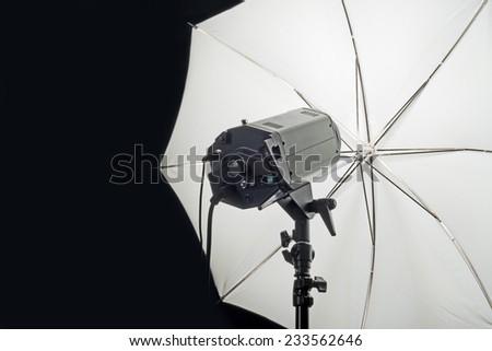 Photography Studio Flash Head with Umbrella and dark black copy space.