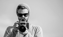 Photojournalist concept. Travel blogger. Professional photographer. Handsome photographer guy retro camera. Guy photographer outdoors sky background. Hipster reporter taking photo. Manual settings.