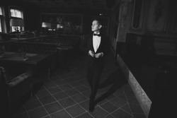 Photos of elegant young man in suit and bowtie walking around the restaurant and buttoning his jacket. Black and white photo