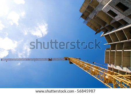 Photos of high-rise construction cranes and unfinished house against the blue sky with clouds. Taken from the bottom up #56845987
