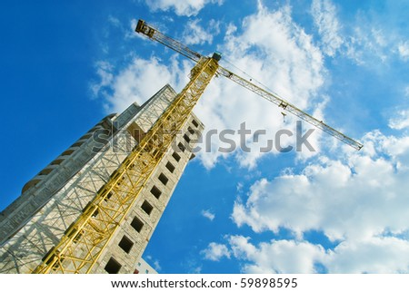Photos of high-rise construction cranes and unfinished house against the blue sky with clouds. Taken from the bottom up