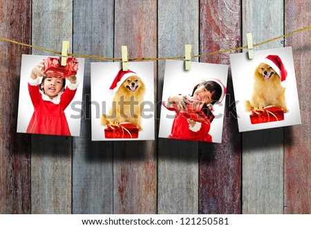 Photos of little girl and dog wearing Santa Claus hat  hanging in the old room.