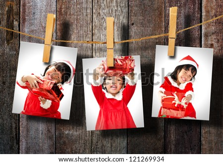 Photos of little girl wearing Santa Claus hat  hanging on wood wall.