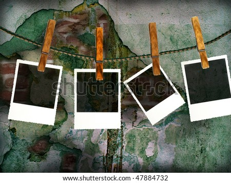 Photos on a clothes line against a grungy stone wall #47884732