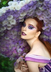 Photoshoot girl and dandelions. Lady in a hat made of dandelions. Glamorous beauty in a lilac hat. Lilac makeup. Fantasy image. Young model and dandelions