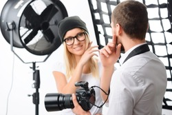 Photoshoot issues. Young male photographer talks with female model about important photoshoot issues