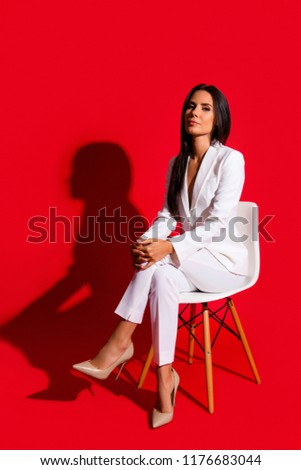 Stock Photo Photoshooting studio concept. Vertical portrait of proud arrogant woman sitting on chair leg by foot looking at camera isolated on vivid red background