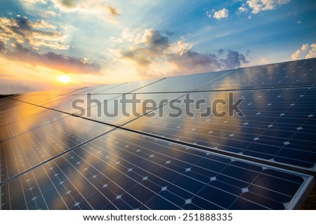 Photovoltaic modules on the background of sunset and cloudy sky