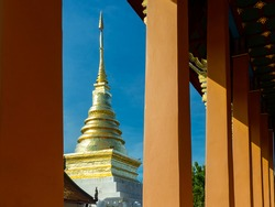 Phra That Chang Kham looking through chapel's pillars : The golden pagoda of Buddha's relics at Wat Phra That Chang Kham. A famous temple in northern Thailand. Tourist destination in Nan province.