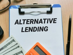 Phrase ALTERNATIVE LENDING written on paper clipboard with pen,calculator,fake money and eye glasses. Business and economy concept.