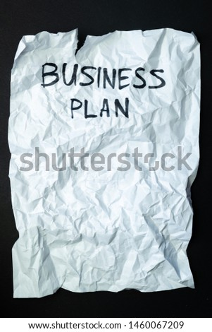"""Phrase """"business plan"""" handwritten on crumpled torn paper, top view. Sign, concept of failed plans or poor management, abstract illustrative image #1460067209"""