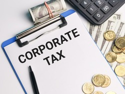 Phrase CORPORATE TAX written on paper clipboard with calculator,a pen,coins and fake money. Business and finance concept.