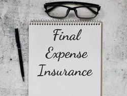 Phrase Final Expense Insurance written on note book with pen and eye glasses. Business concept.