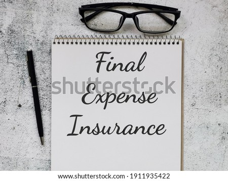 Phrase Final Expense Insurance written on note book with pen and eye glasses. Business concept. Foto d'archivio ©