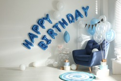 Phrase HAPPY BIRTHDAY made of blue balloon letters in decorated room