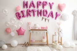 Phrase HAPPY BIRTHDAY made of pink balloon letters in decorated room