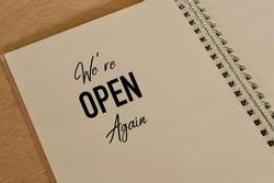 Phrase WE'RE OPEN AGAIN written on notebook