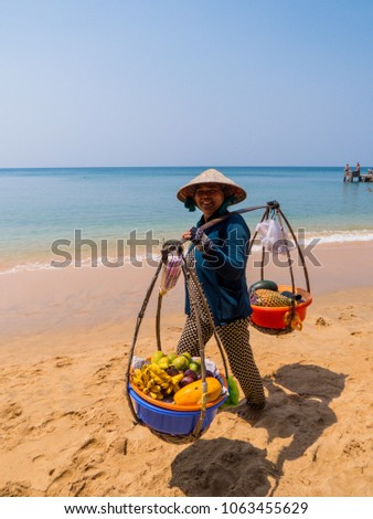 PHU QUOC, VIETNAM - FEBRUARY 13, 2018: Unidentified woman selling fruit on the beach.  #1063455629