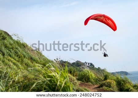 Phuket, Thailand - October 6, 2014 : Paraglider flying over the hill side in clear sky on Phuket Island, Thailand. Phuket is a very famous Island in Thailand