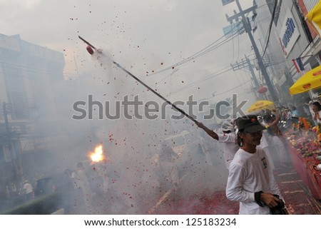 PHUKET TOWN - OCT 4: Devotees of a Taoist shrine carry a God idol on a palanquin while participating in a street procession of the Phuket Vegetarian Festival on Oct 4, 2011 in Phuket Town, Thailand.