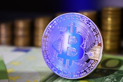 Physical Bitcoin BTC coin on a background with money