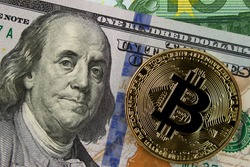 Physical bitcoin lies on one hundred dollar and one hundred euro bills