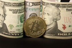 Physical bitcoin next to ten, twenty and fifty dollar bills
