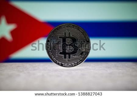 Physical silver version of Bitcoin (BTC) and Cuba Flag on the background. Conceptual image for investors in cryptocurrency and Blockchain Technology. #1388827043
