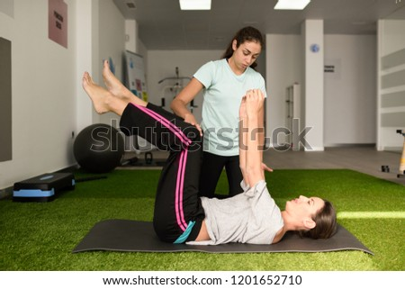 Physical therapist assisting young caucasian woman with exercise during rehabilitation in the gym at hospital. Female physiotherapist training a patient in physiotherapy center.