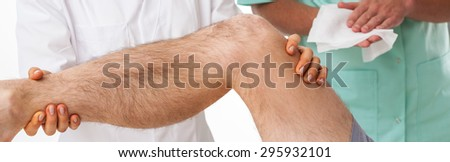 Physical therapist exercising with patient after knee injury