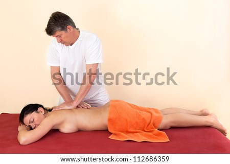 Physical therapist giving a young woman a back massage in a health center