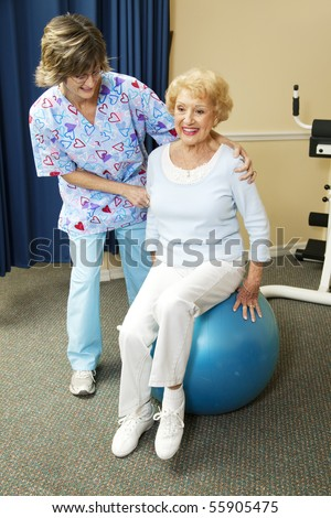 Physical therapist helps a senior woman exercise on a pilates ball.