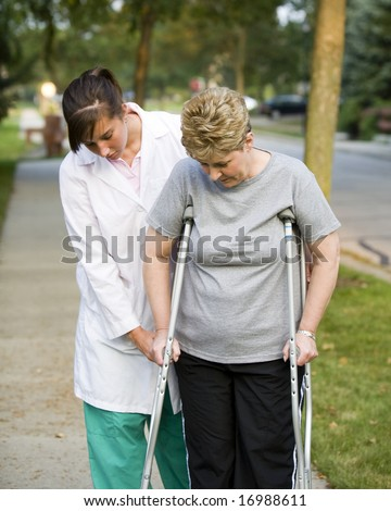 physical therapist helps a woman on crutches