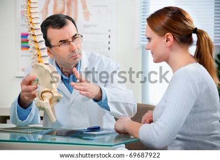 Physical Therapist shows the problem areas on the model of the spine to patient and explains the cause of her pain.