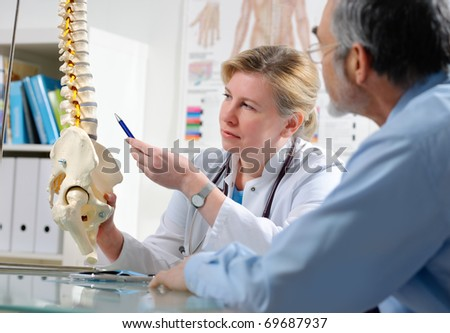 Physical Therapist shows the problem areas on the model of the spine to patient and explains the cause of his pain.